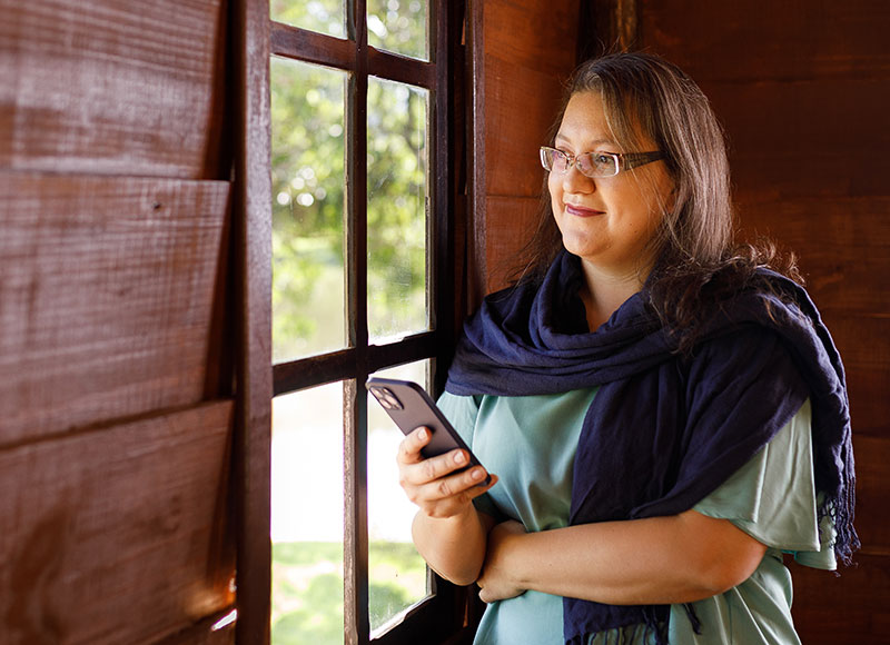 Woman looking outsite holding her phone