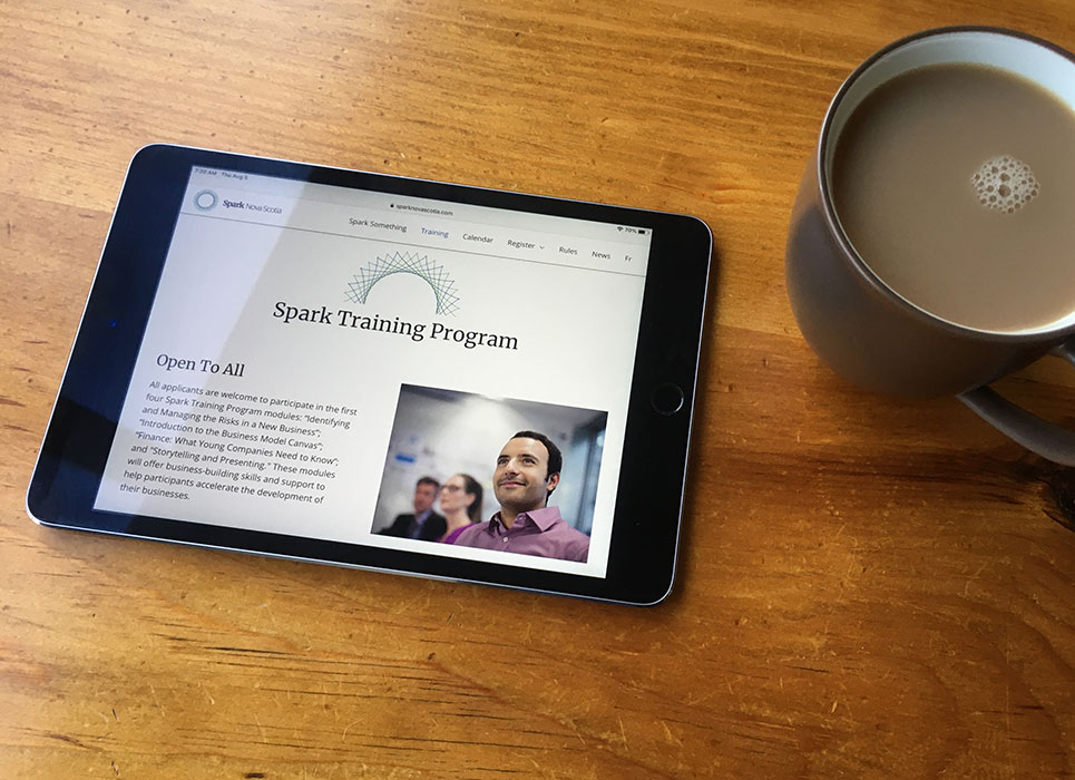 Spark website on tablet next to coffee mug